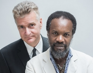 David McAlmont & Alex Webb in suit jackets and looking straight at the camera, on a plain white background.