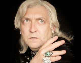 Clinton Baptiste against a black background, hand placed on his shoulder, looking past the camera