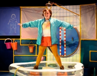 A girl stands in a star position inside a paddling pool beneath an oversized showerhead