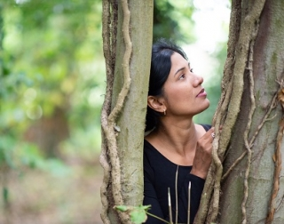 A South Asian woman standing between two trees and looking to the left.
