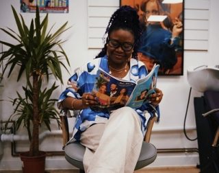 A woman sits in a chair reading a magazine.