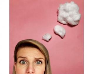 The top of a woman's head. She looks confused and thought bubbles made of cotton wool come from her head against a pink background.