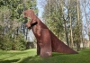 A dinosaur sculpture on a green field.