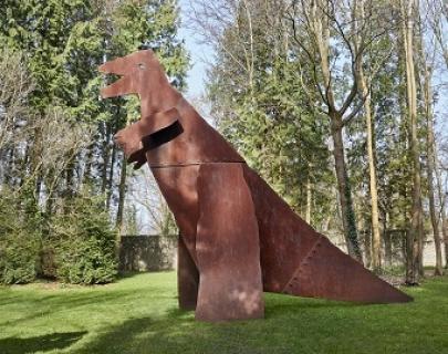 A dinosaur sculpture on a green field.