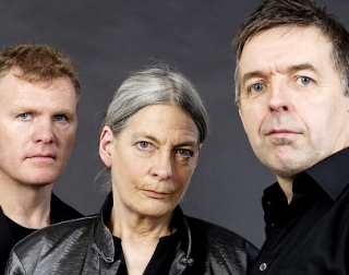 Two men and a woman look into the camera, stern faced in front of a grey background