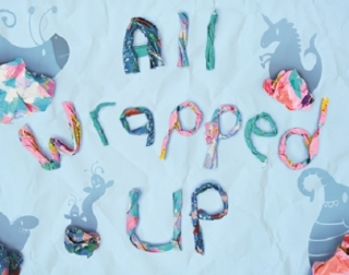 Wrapping paper scrunched up on a light blue background which reads All Wrapped Up