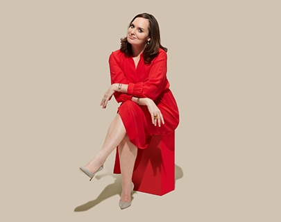 A woman sat down in a red dress on a beige background