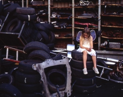 A child in a white dress and fairy wings sits on a pile of tyres and looks at the floor