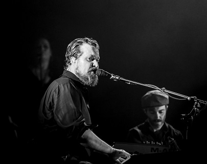 A black and white image of John Grant onstage.
