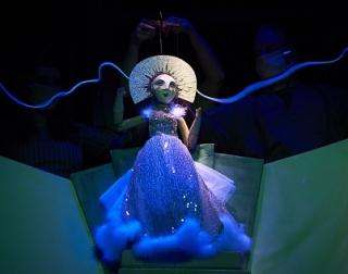 A female puppet wearing a dress