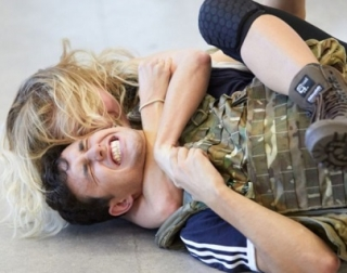 A man and woman perform stage combat on the floor. The man looks in pain and the woman's arms are around his neck.