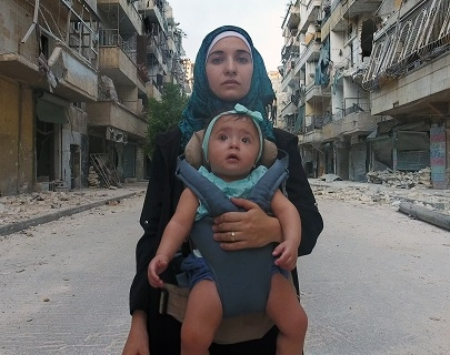 A photo of a woman carrying her baby set against the rubble and ruins of Aleppo