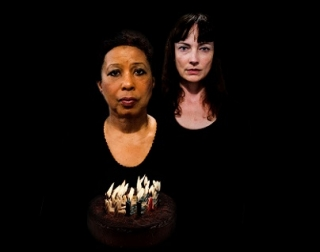 A photo of two women, both wearing black, looking directly at the camera with sorrowed expressions