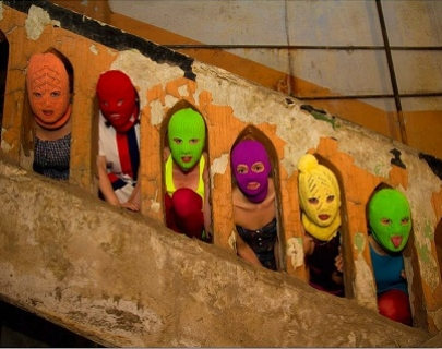 Faces looking through gaps in a staircase with brightly coloured face masks on