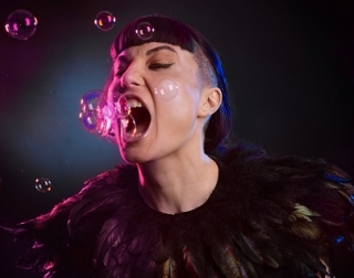 A woman wearing black feathers opening her mouth to eat pink bubbles