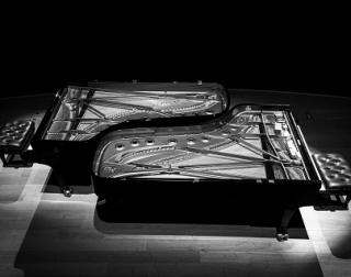 A grey scale photo of two grand pianos slotted together like a jigsaw with a piano stool on either end