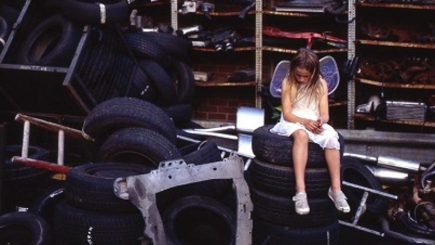 A girl in a white dress and fairy wings sits on a pile of tures and looks at the floor