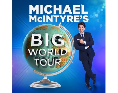 A man in a suit smiles and points to an oversized globe. The writing reads: Michael McIntyre's Big World Tour