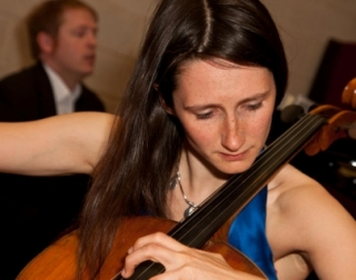 A photo of a woman in a blue dress playing the cello