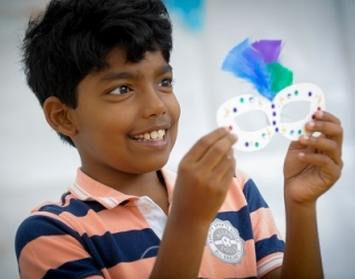 A smiling child holds an eye mask that has been decorated with gems and multi-coloured feathers