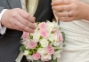 A bouquet of flowers held by two hands wearing wedding rings and holding champagne flutes