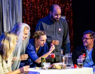 A group of people round a table holding shot glasses, one is wearing a wedding veil