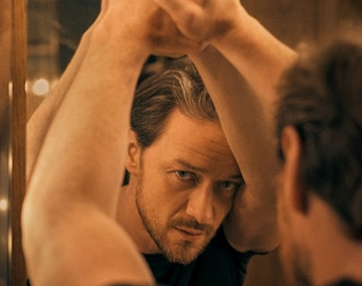 A man in a black t-shirt leaning on a mirror and looking at his reflection.