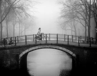 Black and white. A woman rides a bike over a canal bridge. It is foggy, and there are trees and buildings in the background.