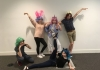A group of youth theatre performers pose for the camera, wearing colourful wigs.