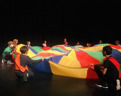 A group of children kneel around a brightly coloured piece of fabric on the floor
