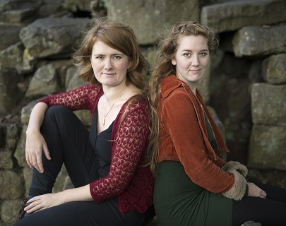 Two women sit back to back in front of a wall looking at the camera