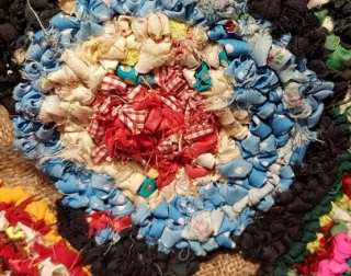 A photo of different coloured fabrics woven together into a rag rug