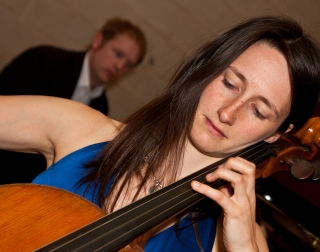 A woman in a blue dress with long hair plays the cello