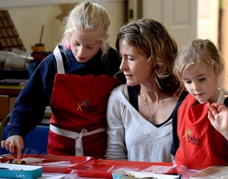 A woman and two girls wearing aprons sit and stand behing a table and make chocolate