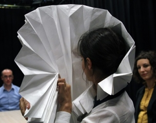 A woman with dark hair holds a large white paper fan in front of her face, watched by audience members.