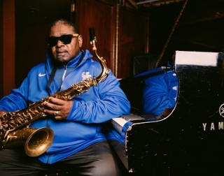 A man in a blue hoodie and sunglasses sat at a piano stall with alto saxophone in hand