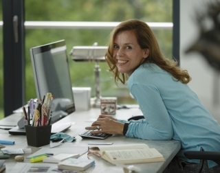 A blonde woman in a blue shirt sits at a computer desk, smiling at the camera.
