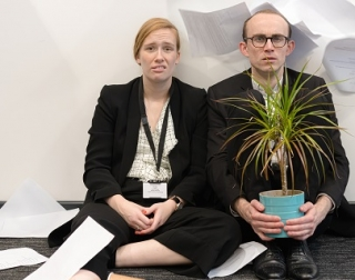 Two people wearing suits sit on a dishelved office floor wearing suits and holding a pot plant