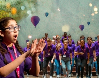 A child sings in the foreground. The background shows a choir of young people, with illustrations of hot air balloons behind them.