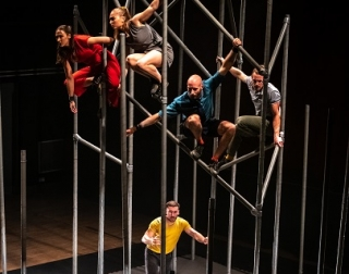 4 performers crouch on poles of scaffolding, high above a performer below