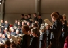A choir stands in rows, looking at sheet music.
