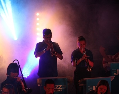 "Young people playing brass instruments are backlit by blue and purple lights. ""Jazz Matters"" banners hang on their music stands."