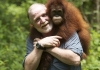 A man carrying an orangutan round his shoulders in the rainforest