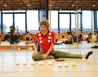 A man sits on the floor in front of a mirror, looking down at some juggling balls in front of him.