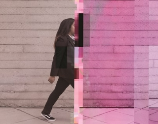 An image of a young person in a school uniform walking in front of a brick wall. The image splits in the middle, showing the person disappearing as the image pixelates and turns pink.