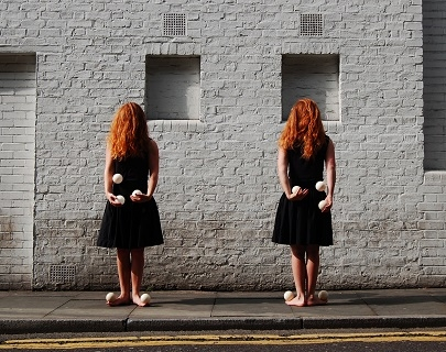 Two girls with red hair over their face wear dresses and juggle