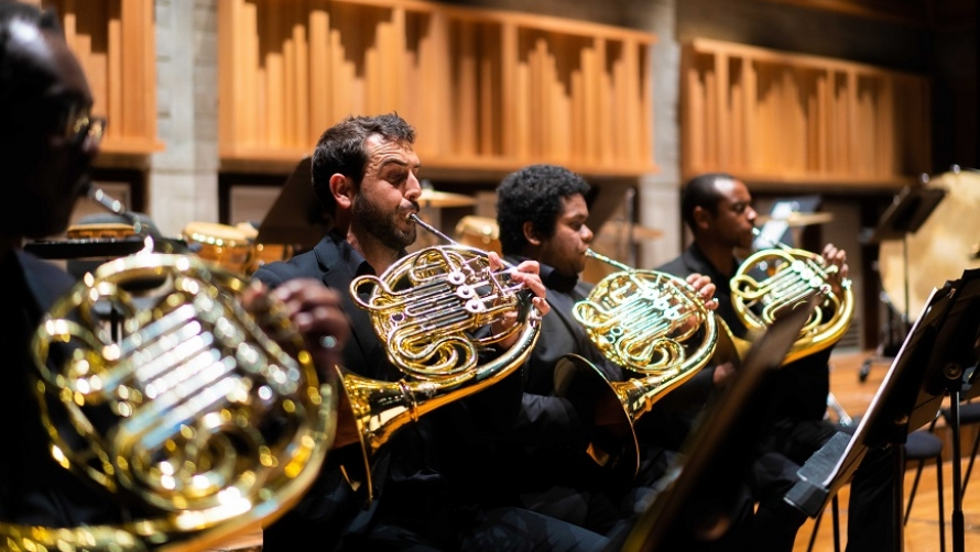An image of four men sat playing the french horn