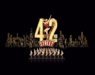 """The skyline of a city at night, with a dancer posing in the words """"42nd Street"""" and a chorus of dancers in front of it."""