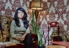 A woman sits on a sofa in a room with patterned wallpaper behind her
