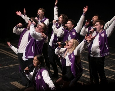 A group of young people in purple jackets, holding microphones and singing, with their hands in the air.